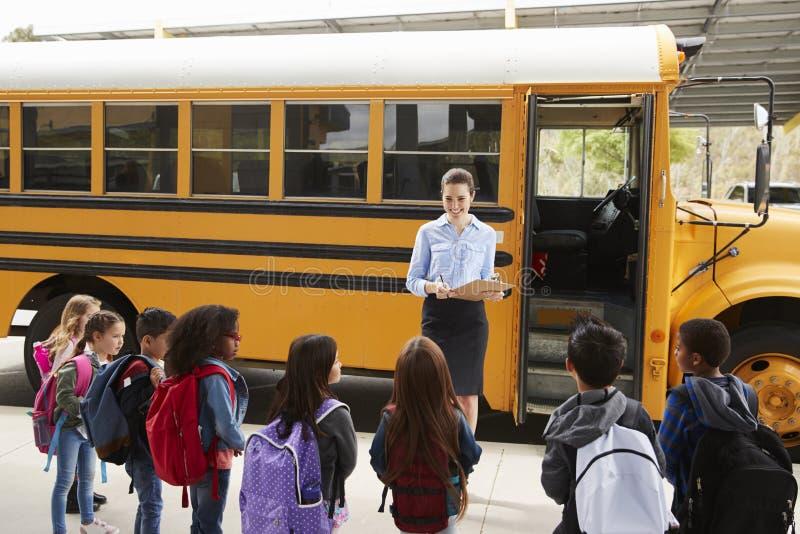 Nauczyciel bierze rejestr szkoła dzieciaki autobusem szkolnym zdjęcia royalty free