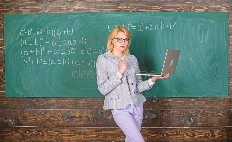 Nauczyciel blondynki kobieta z nowo?ytnym laptopu surfingu interneta chalkboard t?em Szkolna innowacja Dystansowa edukacja obrazy royalty free