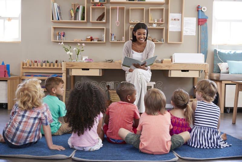 Nauczyciel Czyta dzieci Przy opowieść czasem Przy Montessori szkołą fotografia royalty free