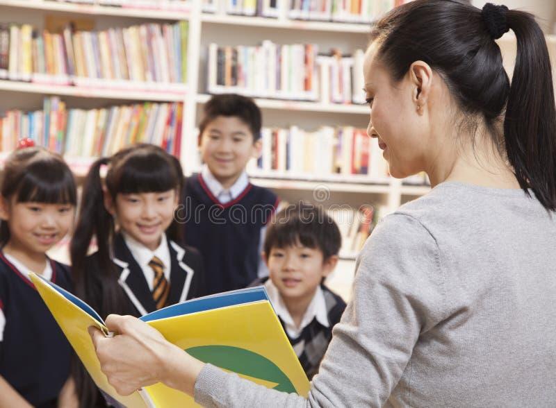 Nauczyciel czyta jej szkoła podstawowa ucznie obrazy stock