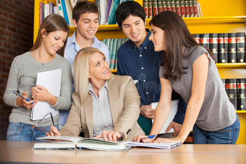 Nauczyciel Dyskutuje Z uczniami Wewnątrz Przy stołem obrazy royalty free