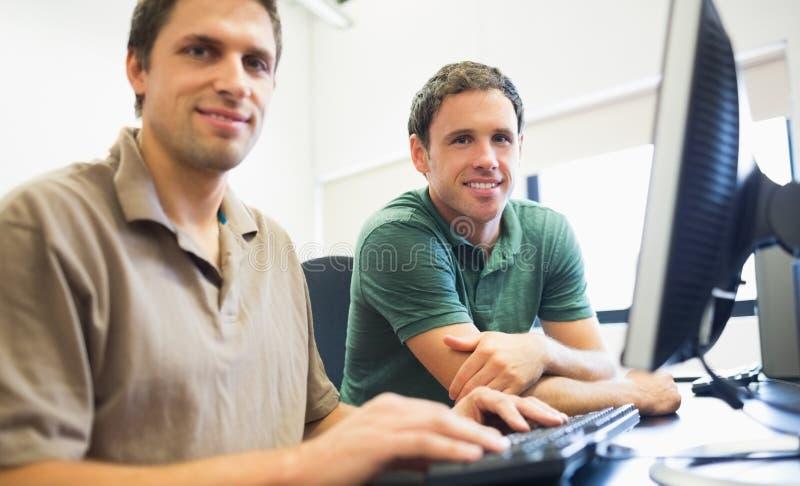 Nauczyciel i dojrzały uczeń w komputerowym pokoju fotografia stock