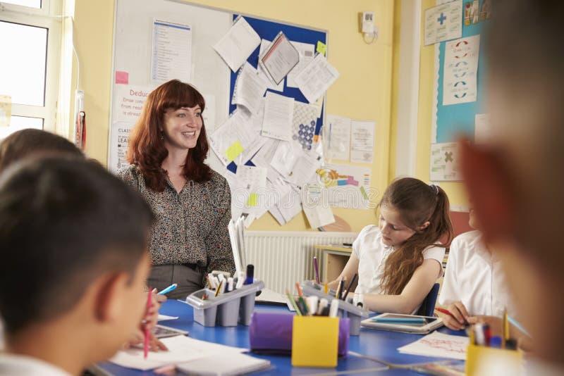 Nauczyciel i dzieciaki pracujemy na klasowym projekcie, zamykamy up fotografia stock
