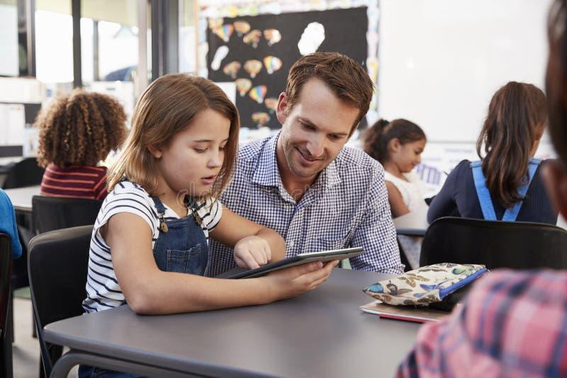 Nauczyciel i potomstwo uczennica używa pastylkę w sala lekcyjnej fotografia royalty free