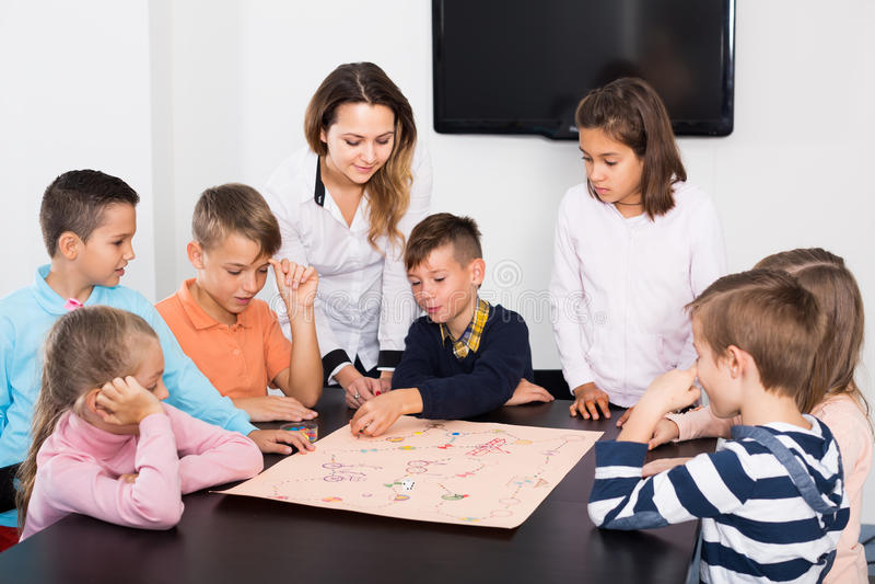 Nauczyciel i szczęśliwi dzieciaki myśleć przy stołem w sala lekcyjnej obrazy royalty free