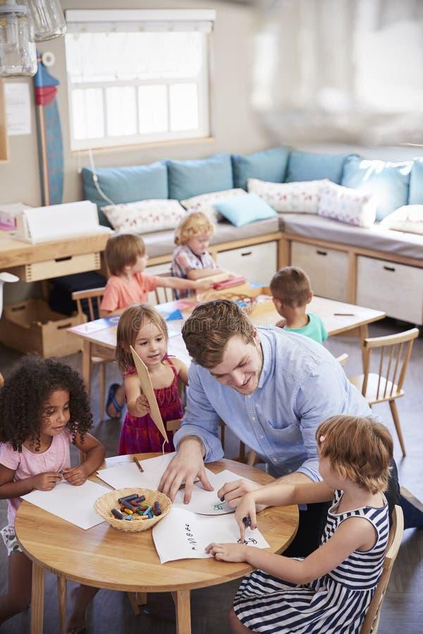 Nauczyciel I ucznie Ćwiczy Pisać W Montessori szkole obraz royalty free