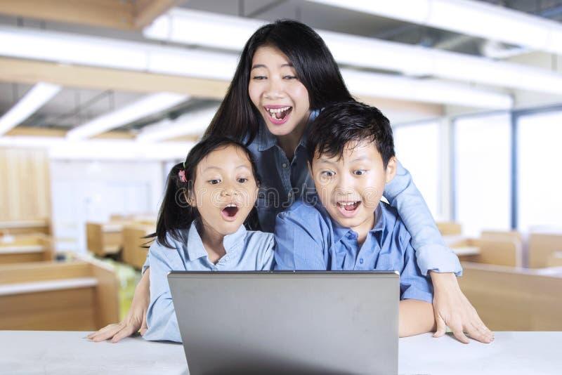 Nauczyciel i ucznie patrzeje laptop zdjęcie stock