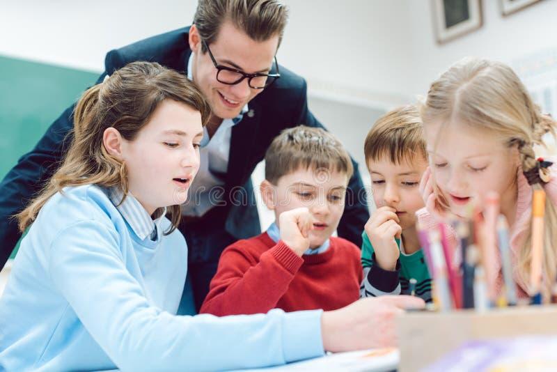 Nauczyciel i ucznie pracuje wpólnie w sesji grupy lub drużyny zdjęcie royalty free