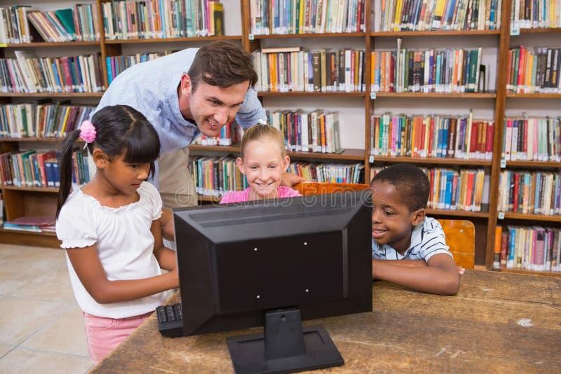 Nauczyciel i ucznie używa komputer przy biblioteką zdjęcie royalty free