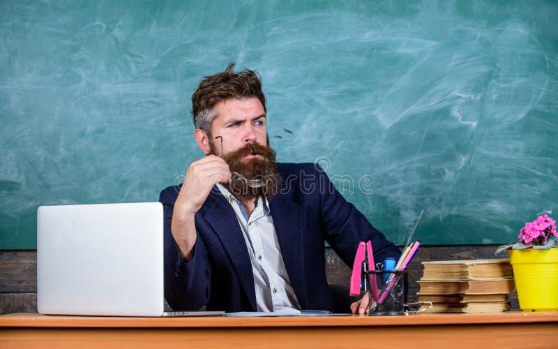 Nauczyciel koncentrował brodatego dojrzałego schoolmaster słuchanie z uwagą Nauczyciel formalna odzież siedzi stołową sala lekcyj fotografia royalty free