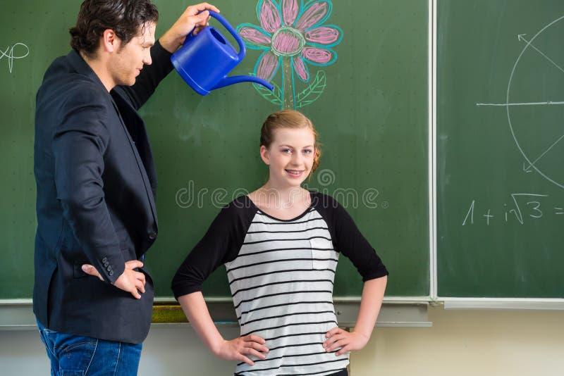 Nauczyciel motywuje szkolnego ucznia przed deską obraz stock