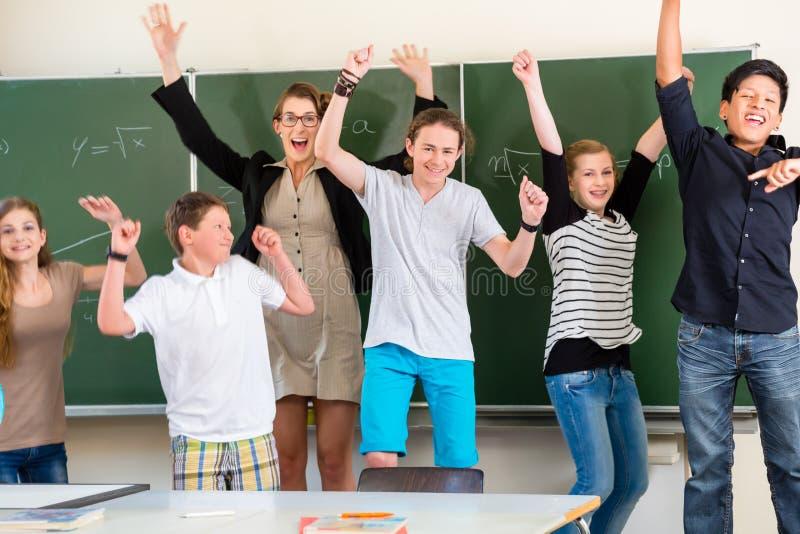 Nauczyciel motywuje uczni w szkolnej klasie zdjęcie royalty free