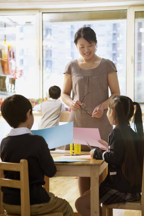 Nauczyciel opowiada ucznie robi sztuce w sala lekcyjnej fotografia stock