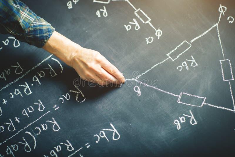 Nauczyciel pisze na desce z kredą formule dla elektrycznego prądu zdjęcie stock