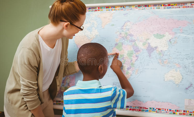 Nauczyciel pomaga chłopiec czytać mapę w sala lekcyjnej fotografia stock