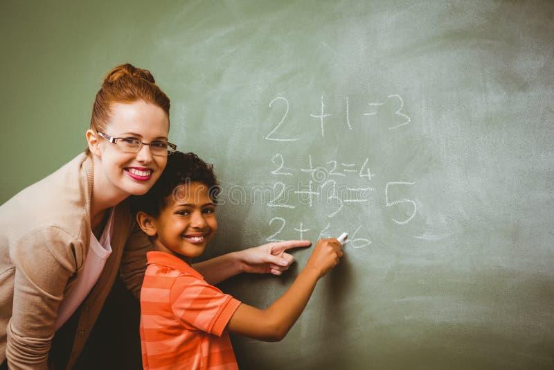 Nauczyciel pomaga chłopiec pisać na blackboard w sala lekcyjnej obrazy royalty free