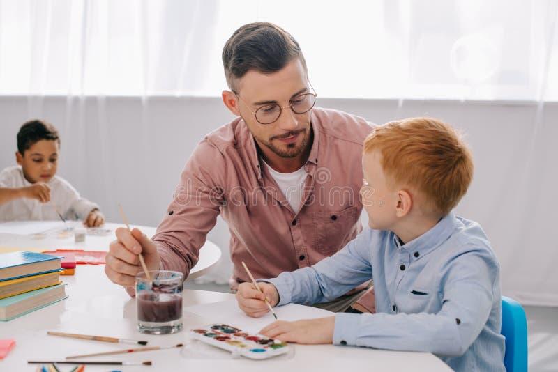nauczyciel pomaga chłopiec rysować obrazek przy stołem obraz royalty free
