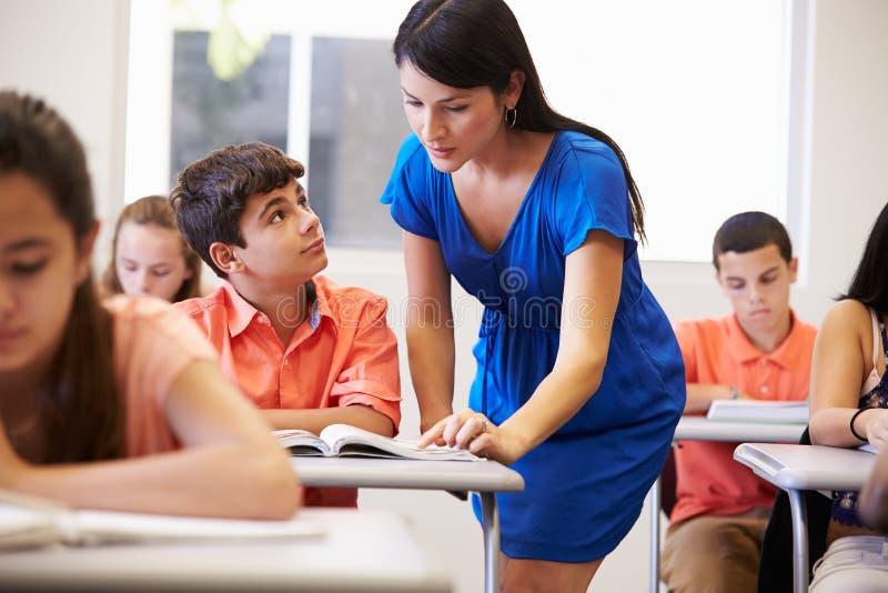 Nauczyciel Pomaga Męskiego szkoła średnia ucznia W sala lekcyjnej obrazy stock