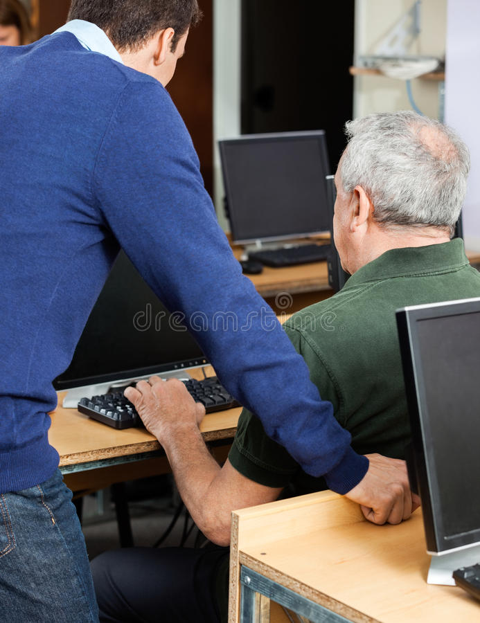 Nauczyciel Pomaga Starszego mężczyzna Przy Komputerowym biurkiem obrazy stock