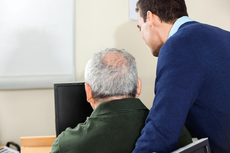 Nauczyciel Pomaga Starszego mężczyzna W komputer klasie obrazy stock