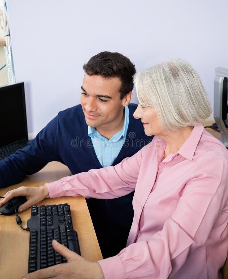 Nauczyciel Pomaga Starszej kobiety W Używać komputer fotografia royalty free