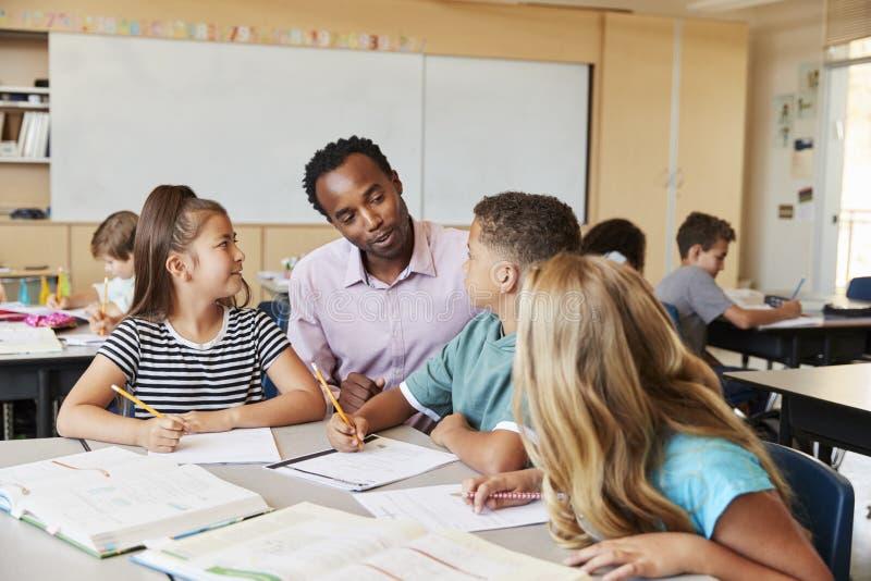 Nauczyciel pracuje z szkoła podstawowa dzieciakami przy ich biurkiem fotografia royalty free