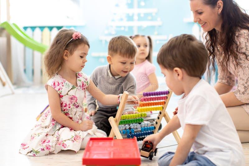 Nauczyciel przedszkola i dzieci bawiące się abakusem siedzącym na podłodze zdjęcia stock