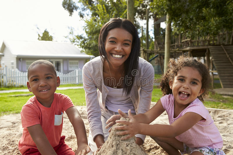 Nauczyciel Przy Montessori szkołą Bawić się Z dziećmi W piasek jamie obrazy royalty free