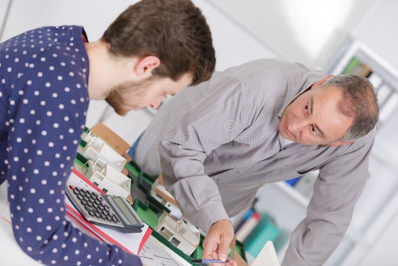 Nauczyciel sprawdza coursework ucznia w szkole biznesu zdjęcia royalty free