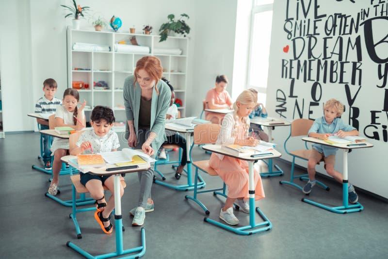 Nauczyciel sprawdza pracę domową jej ucznie w klasie zdjęcie royalty free