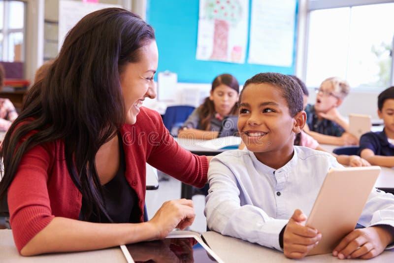 Nauczyciel szkoły podstawowej pomaga chłopiec używa pastylka komputer obraz royalty free