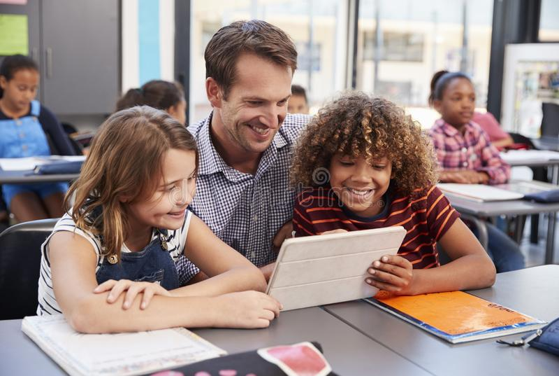 Nauczyciel używa pastylkę z dwa uczniami w szkolnej klasie zdjęcia royalty free