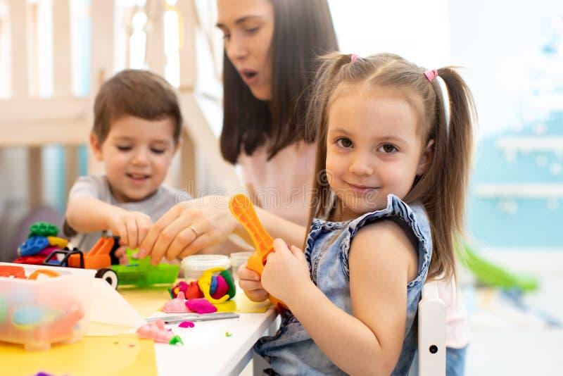 Nauczyciel uczy dzieci rękodzieła w przedszkolu lub szkole zabaw obraz royalty free