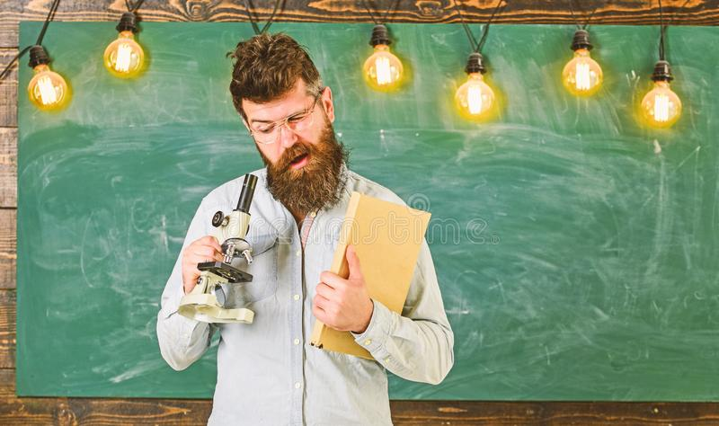 Nauczyciel w eyeglasses chwytach książka i mikroskop Mężczyzna z brodą i wąsy na ruchliwie twarzy badania naukowego pojęcie zdjęcia royalty free