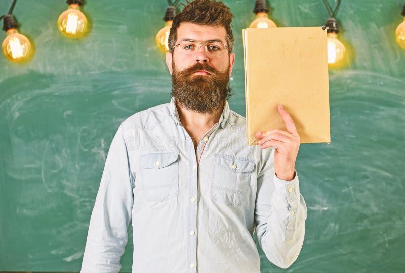 Nauczyciel w eyeglasses chwytach rezerwuje w ręce, kopii przestrzeń Mężczyzna z brodą i wąsy na spokojnych twarz stojakach w sala obrazy stock
