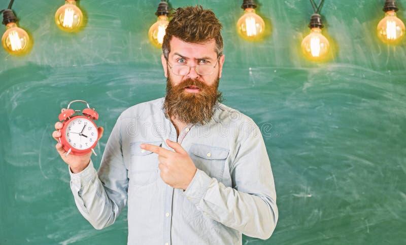 Nauczyciel w eyeglasses trzyma budzika Późności pojęcie Mężczyzna wskazuje przy zegarem z brodą i wąsy na surowej twarzy zdjęcia royalty free