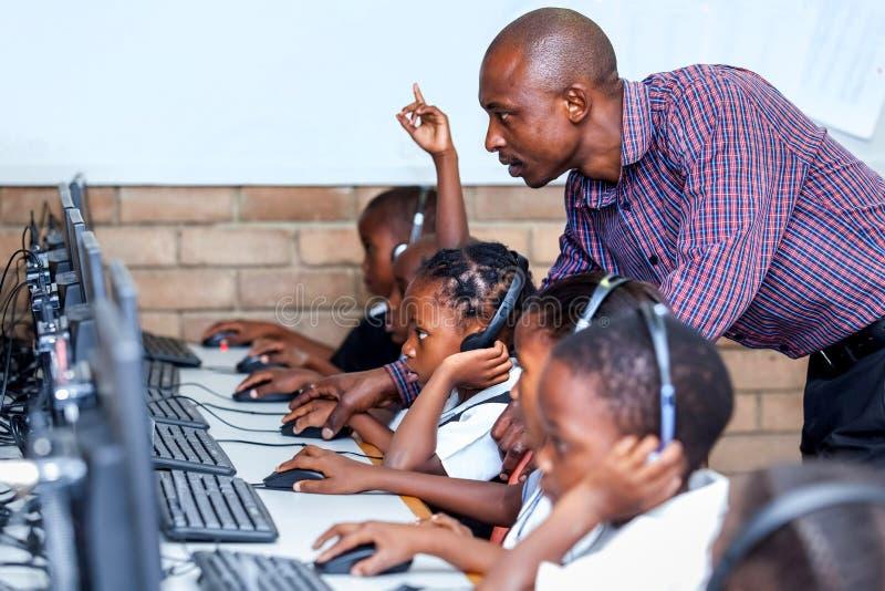Nauczyciel w sala lekcyjna seansie żartuje komputerowe umiejętności obrazy stock