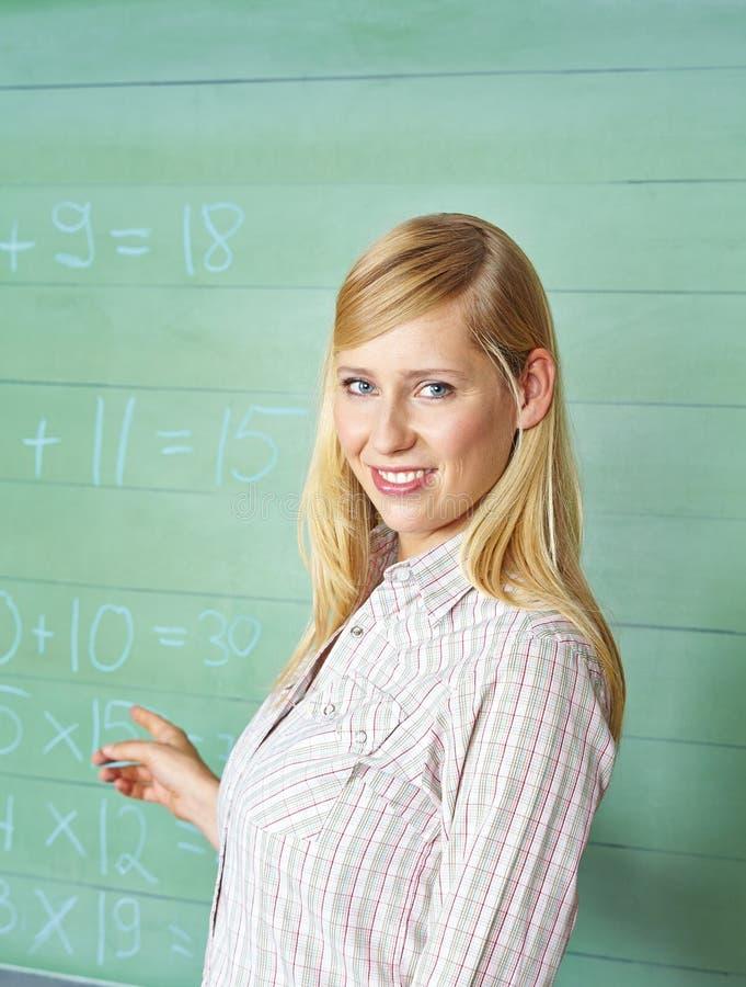 Nauczyciel wskazuje chalkboard w szkole zdjęcia royalty free