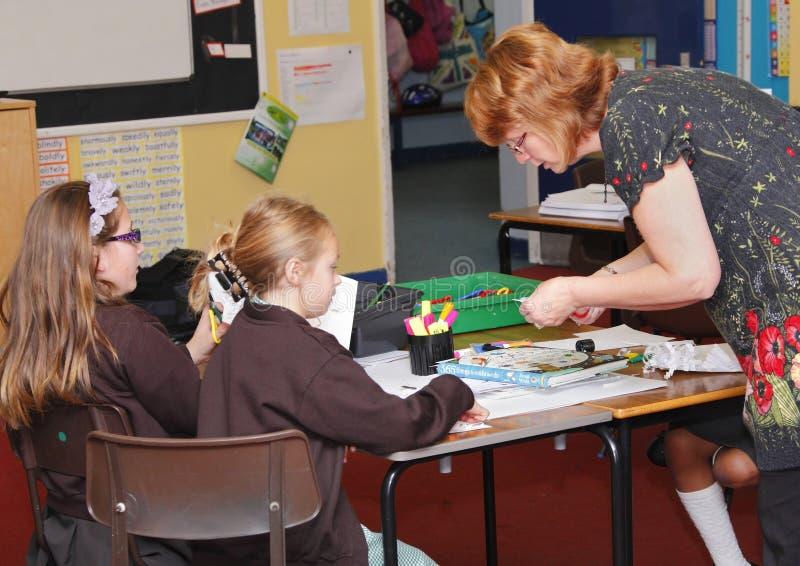 Nauczyciel z dziećmi w sala lekcyjnej obrazy stock