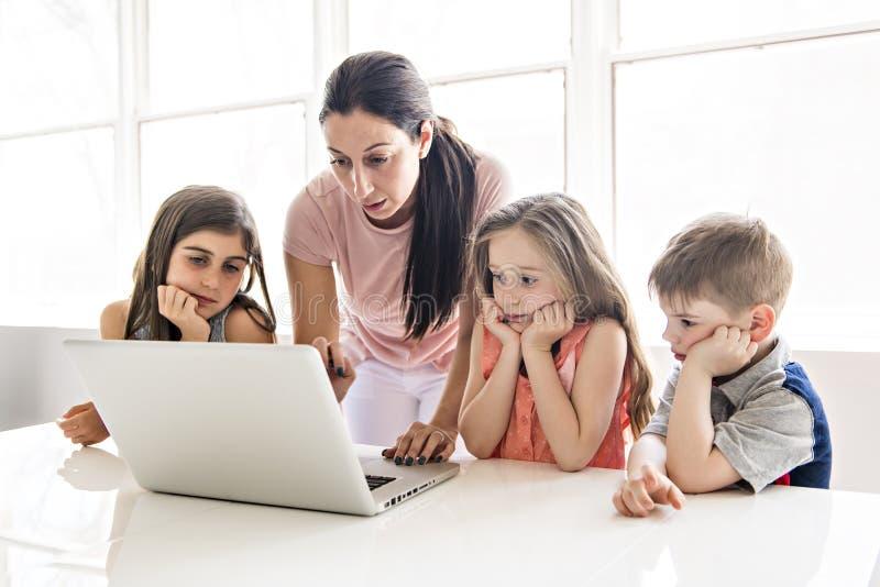 Nauczyciel z grupą dzieci w wieku szkolnym z laptopem na przodzie obrazy stock