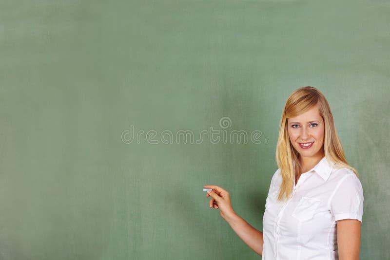 Nauczyciel z kredą przed chalkboard zdjęcia stock