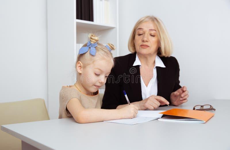 Nauczyciel z ma?? dziewczynk? Robi? pracy domowej poj?ciu zdjęcia stock