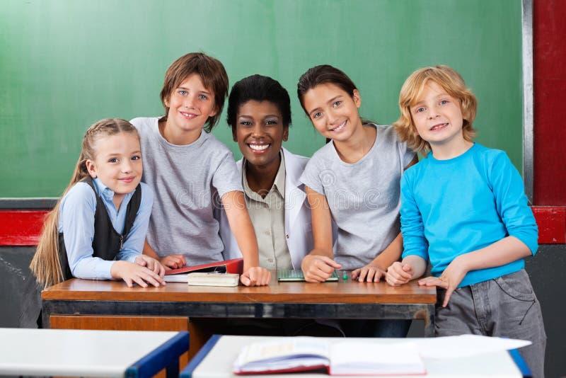 Nauczyciel Z uczniami Przy biurkiem W sala lekcyjnej fotografia royalty free