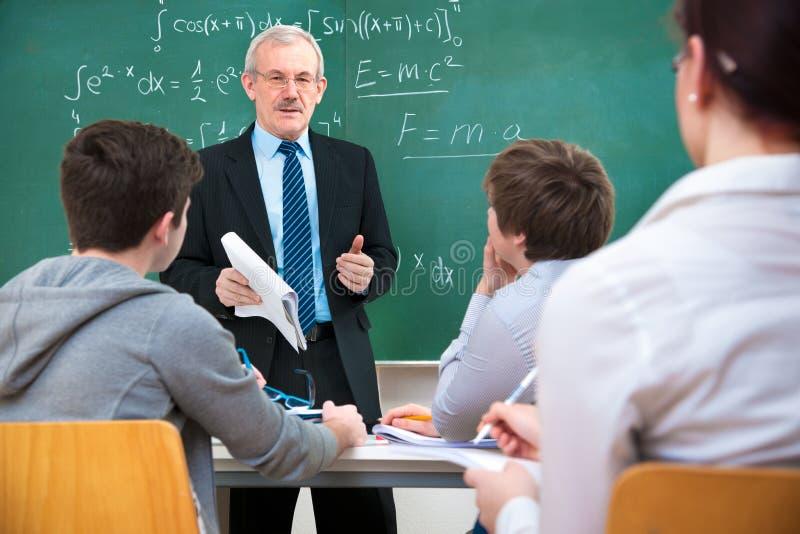 Nauczyciel z uczniami w sala lekcyjnej obrazy stock