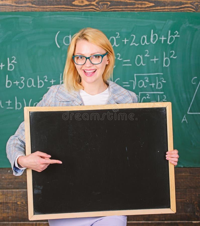 Nauczyciela chwyta blackboard reklamy kopii pusta przestrze? Informacja dla przybywaj?cych uczni Nauczyciela przedstawienia szko? zdjęcie royalty free