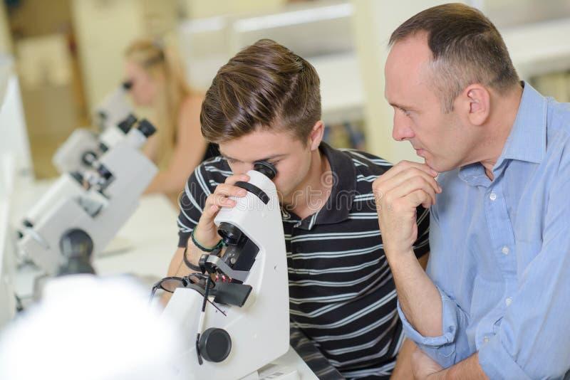 Nauczyciela dopatrywania studencki spojrzenie w mikroskop obrazy royalty free