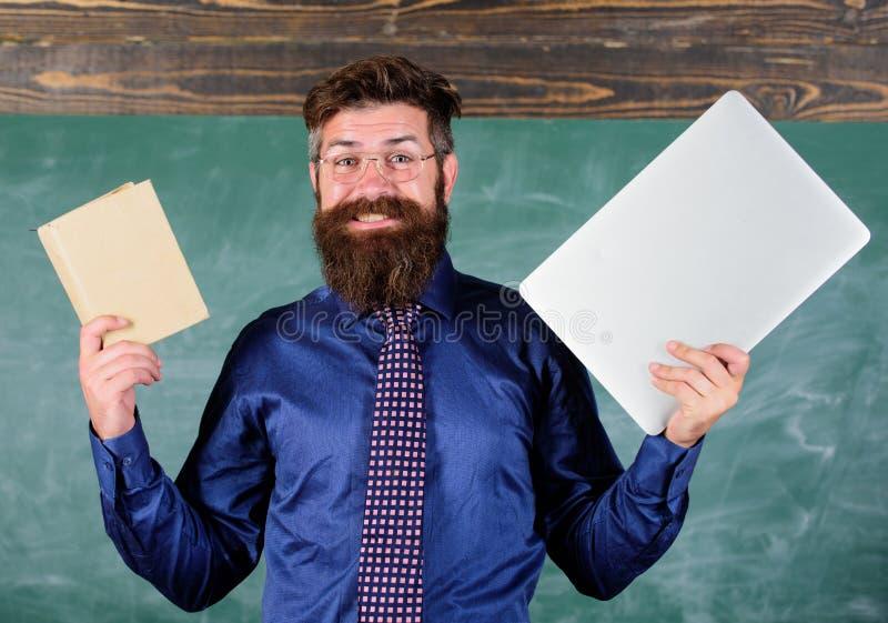 Nauczyciela modnisia brodaci chwyty książka i laptop Co ty wolał Digital przeciw papierowi Nauczyciela wybierać nowożytny obraz stock