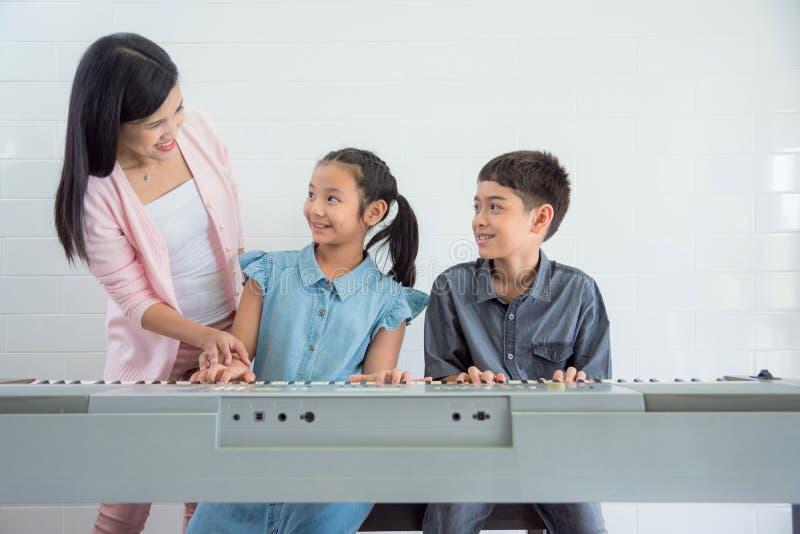 Nauczyciela nauczania ucznie bawić się klawiaturę przy szkołą zdjęcia royalty free