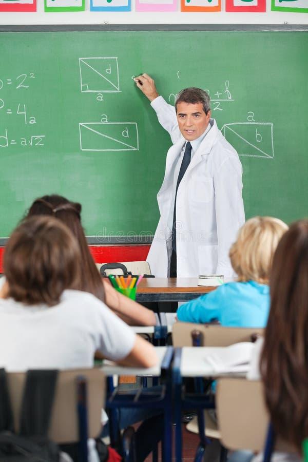 Nauczyciela nauczanie Podczas gdy Pisać Na Pokładzie zdjęcia royalty free
