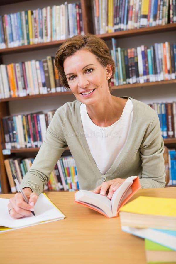 Nauczyciela writing na notepad przy biblioteką obraz royalty free